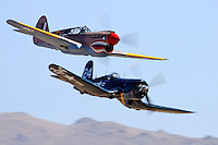 """John Curtiss Paul in the P-40E Warhawk """"Sneak Attack"""" passes """"Race 24"""" piloted by Jimmy Leeward during the 2009 Unlimited Bronze Finals. Paul flew the Warhawk to a third place finish with a speed of 324 mph and Leeward flew the Corsair to a 4th place finish at a speed of 323 mph."""