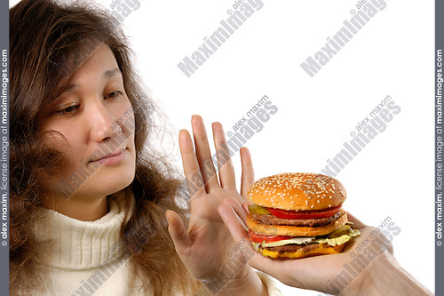 Young woman refusing to eat a hamburger. Showing a stop gesture. Healthy eating and dieting conceptual portrait. Isolated silhouette on white background with copyspace. The woman has half korean half european ethnicity