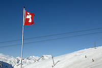 "Switzerland. Valais. Crans Montana. Winter ski resort. Ski lifts are carrying people to the top of the mountain, while other are skiing down the ""Bella Lui"" slopes on a sunny day with blue sky. A swiss flag floats in the air. © 2005 Didier Ruef"