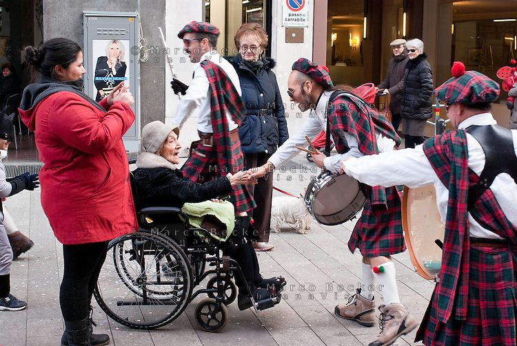 Milano Clown Festival, Festival Internazionale sul Nuovo Clown e Teatro di Strada. Una banda di suonatori in kilt salutano in Corso Garibaldi un'anziana signora in carrozzina --- Milano Clown Festival, International Clown and Street Theatre Festival. Musicians wearing kilt and greeting an old woman on a wheelchair in Garibaldi street
