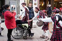 Milano Clown Festival, Festival Internazionale sul Nuovo Clown e Teatro di Strada. Una banda di suonatori in kilt salutano in Corso Garibaldi un'anziana signora in carrozzina --- Milano Clown Festival, International Clown and Street Theatre Festival. Musicians wearing kilt and greeting an old woman on a wheelchair in Garibaldi street