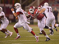 STAFF PHOTO BEN GOFF  @NWABenGoff -- 09/20/14 <br /> Arkansas defensive end JaMichael Winston, right, tackles Northern Illinois quarterback Anthony Maddie during the fourth quarter of the game against Northern Illinois in Reynolds Razorback Stadium in Fayetteville on Saturday September 20, 2014.