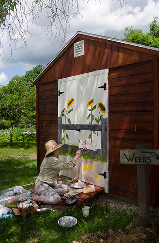 Artist painting mural on door of garden shed in community Garden, Yarmouth Maine USA