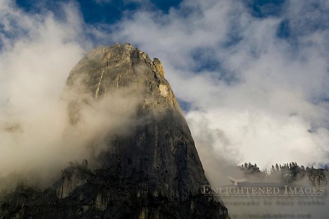Storm clouds shroud the sheer granite cliff of Sentinel Rock at sunset, Yosemite Valley, Yosemite National Park, California