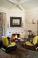 A pair of Art Deco armchairs have been re-upholstered in yellow leather and sit in front of the lit fire in the small sitting room
