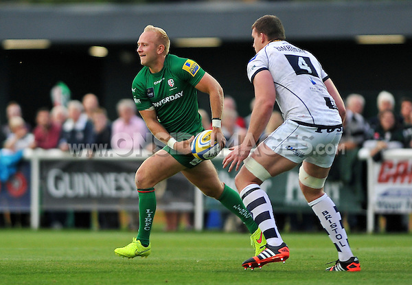 Shane Geraghty looks to pass the ball. Pre-season friendly match, between London Irish and Bristol Rugby on August 22, 2014 at Hazelwood in Middlesex, England. Photo by: Patrick Khachfe / JMP