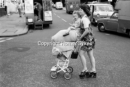Young girl with baby sister returning from shopping trip bags of potatoes Portobello Road, Notting Hill west London UK 1975