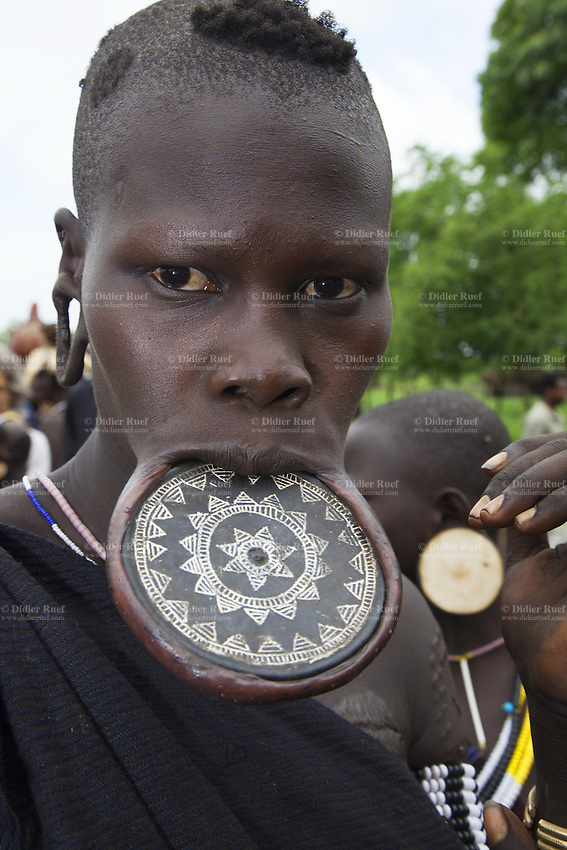 "Ethiopia. Southern Nations, Nationalities, and Peoples' Region. Omo Valley. Mursi tribe. Agro-pastoralist group. Nomadic. Mursi women are known as ""disk-lip"" women. The bottom lip is slit along its full length and the front bottom row of teeth are pulled out to accomodate the ceramic disk which is handmade with a rim around which the stretched lip is pulled. The women are famed for wearing large plates in their lips (round clay plates placed into a cut in the lower lip) and ears. The disk is seen as a symbol of beauty and wealth, and often the younger girls will pierce and strech their ear-lobes, inserting a matching disk in the extended lobe. The Omo Valley, situated in Africa's Great Rift Valley, is home to an estimated 200,000 indigenous peoples who have lived there for millennia. Amongst them are 8'000 Mursi who dwell between the Omo and Mago rivers. Southern Nations, Nationalities, and Peoples' Region (often abbreviated as SNNPR) is one of the nine ethnic divisions of Ethiopia. 11.11.15 © 2015 Didier Ruef"