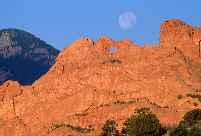 A full moon sits high above the Kissing Camels formation in the Garden of the Gods, CO