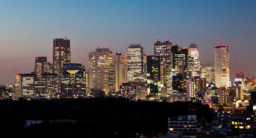 Spectacular panorama of Tokyo`s Shinjuku skyscrapers lit up at dusk.
