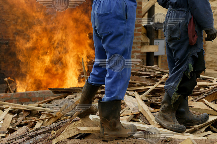 Labourers burning waste wood in a fire at Troutbeck sawmill. The cost of transporting the wood to urbanised areas where it is desperately needed for firewood is unfortunately too high to be economical.