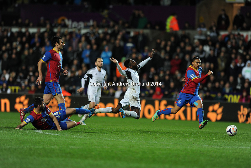 Swansea city's Nathan Dyer is sent flying by the tackle from Joe Ledley of Palace. Barclays Premier league, Swansea city v Crystal Palace match at the Liberty Stadium in Swansea, South Wales on Sunday 2nd March 2014.