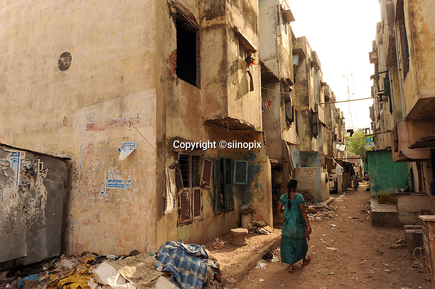 A lady walks on the filthy street in residential area in Madras, India