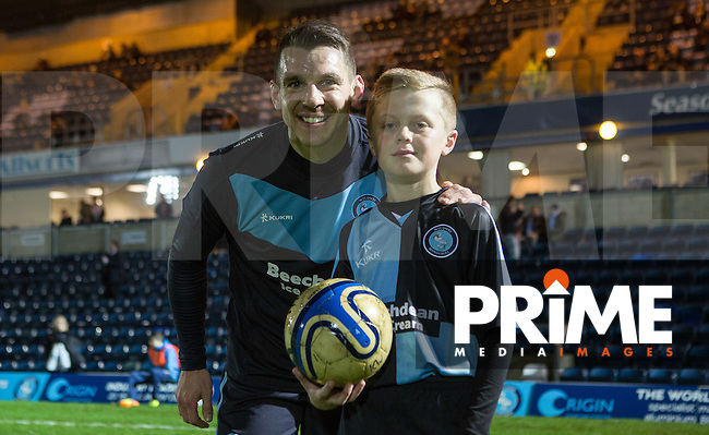 Matt Bloomfield of Wycombe Wanderers with a match day mascot during the Sky Bet League 2 match between Wycombe Wanderers and Notts County at Adams Park, High Wycombe, England on 15 December 2015. Photo by Andy Rowland.