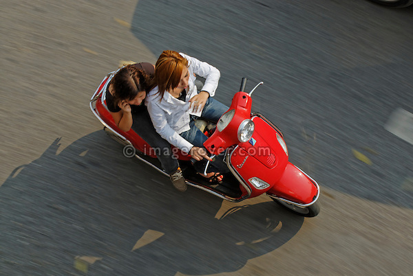 Asia, Vietnam, Hanoi. Hanoi old quarter. Young fashionable vietnamese women riding a red Vespa motorbike through Hanoi.