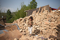 A child stands in front of her distroyed house, outskirts of Kathmandu, Nepal. May 1, 2015