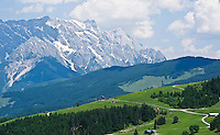 Green alpine hillside and distant peak of Hochkönig (2,941m) in the Northern limestone alps, Austria
