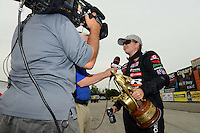Sept. 30, 2012; Madison, IL, USA: NHRA pro stock driver Erica Enders is interviewed by ESPN as she celebrates after winning the Midwest Nationals at Gateway Motorsports Park. Mandatory Credit: Mark J. Rebilas-