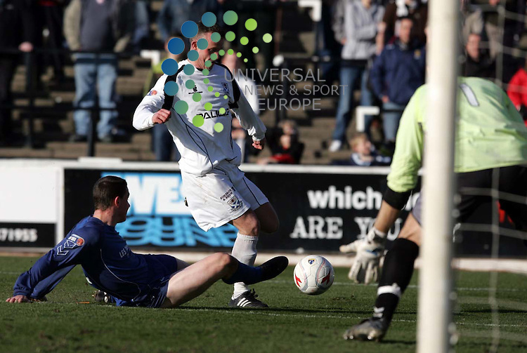 Peterhead's Stuart Smith getting his foot on the ball just as Mark Roberts is set to shoot during the Ayr United V Peterhead. Picture: Universal News And Sport (Scotland). 22/March/2009.
