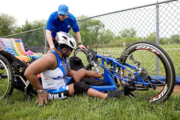 Minda's boyfriend Shawn helps her get into her handcycle in the transition area before the bicycling leg of the New Jersey Devilman Triathlon on May 5, 2012 in Cumberland County, New Jersey.