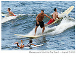 Adult surfer avoids small child on board during crowded conditions at Manasquan's Inlet Beach on Sat., August 7, 2010. There were five first aid calls to this beach due to collisions in the lineup between surfers. This is the only beach designated in Manasquan for surfing.  (8/7/2010)  photo © 2010 ANDREW MILLS