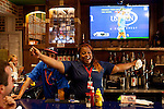 Bartender Saundra Cage leads customers in an Atlanta Braves cheer at the Atlanta Braves All Star Bar and Grill in Concourse D at Hartsfield–Jackson Atlanta International Airport in Atlanta, Georgia on August 28, 2013.