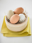 Four eggs of different natural colors in a decorative nest/bowl