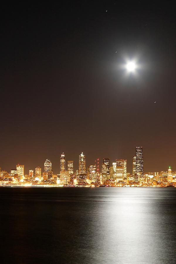 Full moon rising over Seattle city skyline at night, moon reflected in Elliot Bay, Seattle, Washington, USA