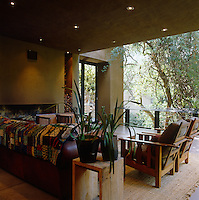 The colours and materials of the open-air sitting room furniture reflect those of the surrounding forest