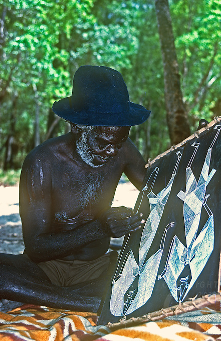 Traditional Australian Aboriginal working on a Bark painting in a remote settlement of Arnhem Land, Northern Territory Australia