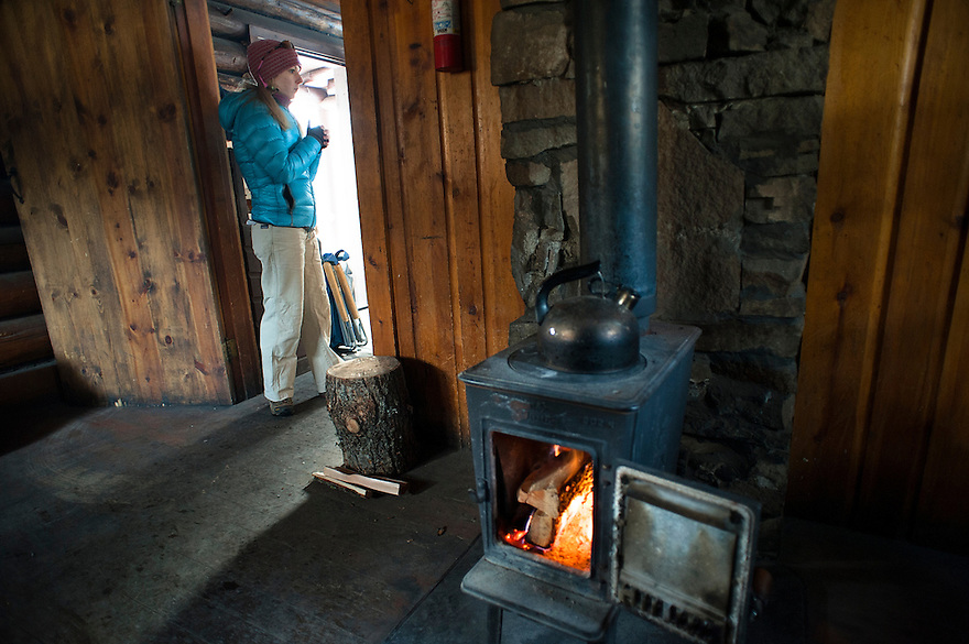 A guest stands in the doorway of the Battle Ridge Cabin in the Bridger Mountains near Bozeman, Montana.