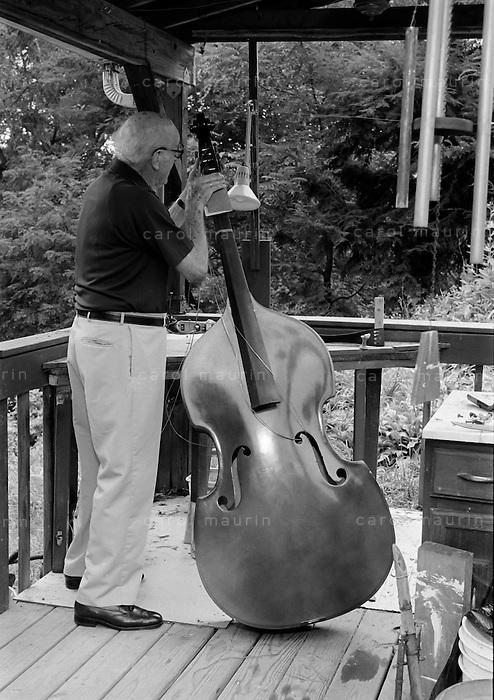 Caucasain elderly man sanding the neck of a string instrument