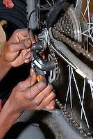 Brescia / Italia 13 novembre 2013<br /> Le mani di Sory Ibrahim Diancoumba (39), rifugiato del Mali, al lavoro nell'officina per riparazioni di biciclette aperta con altri rifugiati con l'aiuto dell'associazione ADL Brescia e con il contributo di Re-Startup, rete nazionale per imprese cooperative di titolari di protezione internazionale vulnerabili.<br /> La Cooperativa Gekake è una delle prime start-up gestite da immigrati richiedenti asilo politico.<br /> Foto Livio Senigalliesi