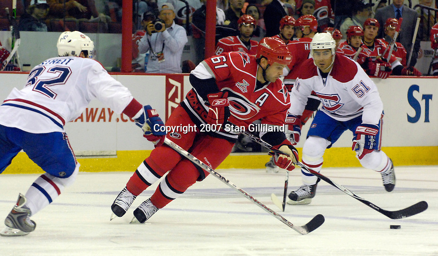 Carolina Hurricanes' Cory Stillman (61) carries the puck through the defense of the Montreal Canadiens' Mark Streit, left, and Francis Bouillon (51) during their game Friday, Oct. 26, 2007 in Raleigh, NC. The Canadiens won 7-4.