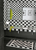 A luxurious black and white tufted rug coordinate with the ceramic tiles on the walls and surfaces if this bathroom