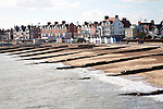 Sandy beach concrete groyne sea defences and historic buildings on the seafront on a sunny day in winter at Felixstowe, Suffolk, England