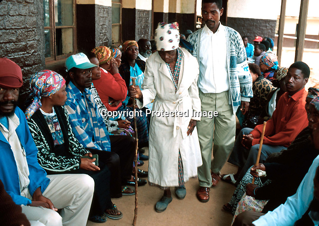 poelec9950081 Politics. Elections. A voting line in Kwa Mashu, a township outside Durban, South Africa. An elderly woman is helped to the voting both. People voted on June 2nd, 1999, the second democratic election in the new South Africa. Elderly, walking stick..Photo: Per-Anders Pettersson /iAfrika Photos