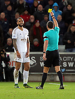 (L-R) Kyle Bartley of Swansea is shown a yellow card by match referee Andrew Marriner during the Barclays Premier League match between Swansea City and Bournemouth at the Liberty Stadium, Swansea on November 21 2015