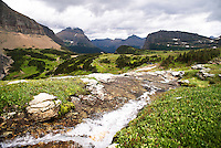 A waterfall tumbles toward Logan Pass as storm clouds gather in Glacier National Park.