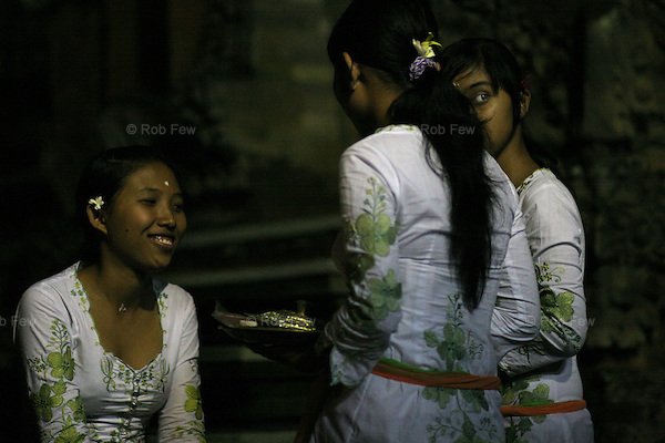 Young girls make offerings at a temple fair in Ubud.