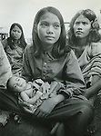 Young Cambodian woman holds baby at refugee camp in Thailand