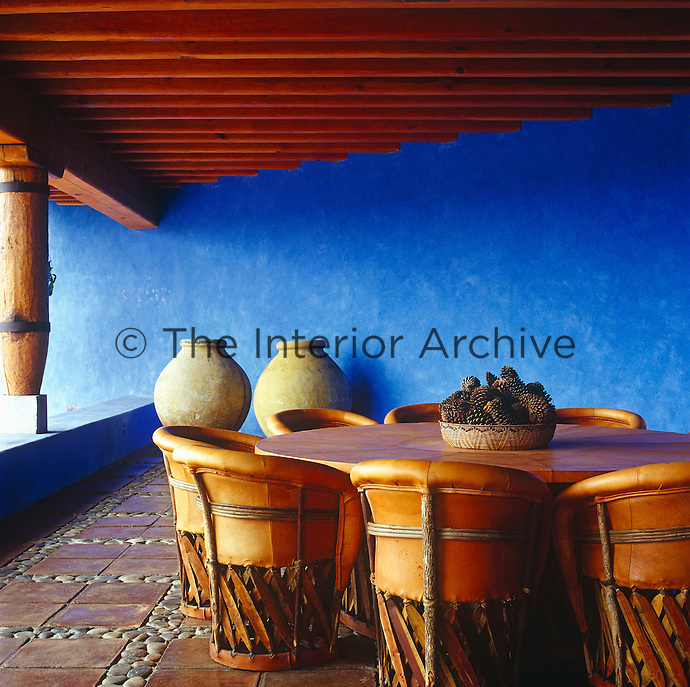 Leather covered chairs grouped around a circular table in the loggia which has bright blue walls