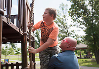 NWA Democrat-Gazette/CHARLIE KAIJO Dan Fuller of Centerton (right) helps Chance Fuller, 10, climb a rope, Monday, August 5, 2019 at McKissic Springs Station playground in Centerton.
