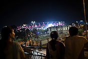 Local residents stand on the overpass and take a look at the main Jawaharlal Nehru Stadium in New Delhi, India.