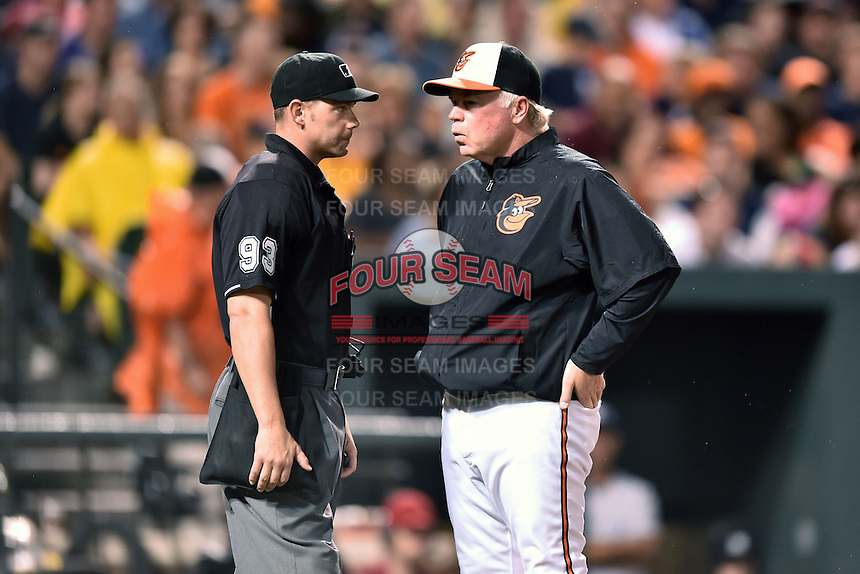 Baltimore Orioles manager Buck Showalter #26 talks with home plate umpire Will Little during a game against the New York Yankees at Oriole Park at Camden Yards August 11, 2014 in Baltimore, Maryland. The Orioles defeated the Yankees 11-3. (Tony Farlow/Four Seam Images)