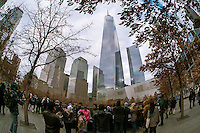 One World Trade Center rises over visitors to the National September 11 Memorial & Museum in New York on Christmas, Thursday, December 25, 2014. The memorial consists of twin memorial pools on the footprints of the World Trade Center and a plaza planted with more than 400 swamp white oak trees. The names of the 2983 victims of 9/11 and the February 1993 WTC attack are inscribed around the base of the pools. (© Richard B. Levine)