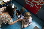MR / Schenectady, NY. Zoller Elementary School (urban public school). Kindergarten classroom. Student teacher shows students how to use iPad to read eBook / app. ID: She4, Man6, Ste14. © Ellen B. Senisi.
