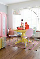 The sweet coloured dining room is painted in succulent shades of pink and yellow