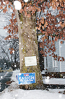 """A campaign for Republican presidential candidate and Ohio governor John Kasich stands near a tree during a snowstorm in Derry, New Hampshire. Above the Kasich sign is a hand-written sign that says """"Dimmock the hypocrite."""" The sign likely refers to Derry Town Councilor Al Dimmock who recently admitted that he'd served time in jail in 1985 for sexual assault. Anonymous signs have been posted around the Derry area referring to the jail time."""