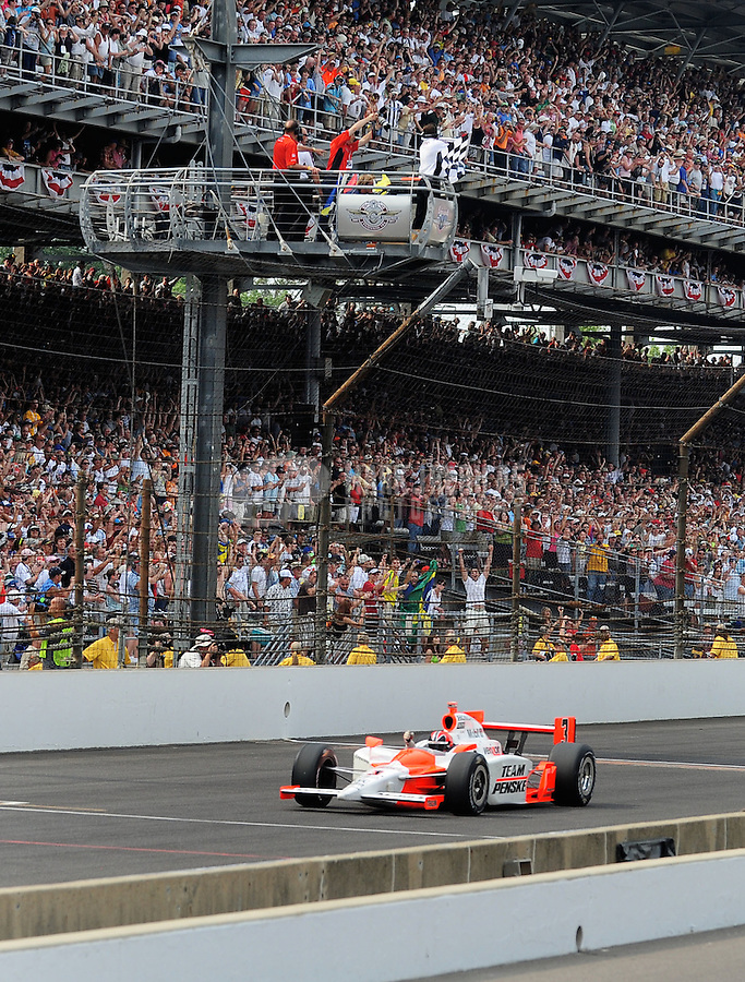May 24, 2009; Indianapolis, IN, USA; IRL driver Helio Castroneves takes the checkered flag to win the 93rd running of the Indianapolis 500 at Indianapolis Motor Speedway.  Mandatory Credit: Mark J. Rebilas-